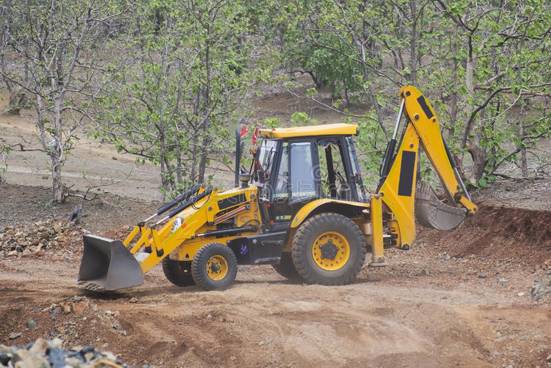 Cavador de la retroexcavadora del cargador en el sitio de la construcción de carreteras imagen de archivo libre de regalías