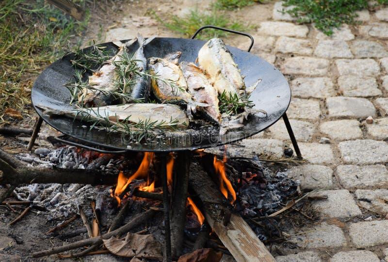 A cavala está grelhando no assado no prato preto do metal no fogo aberto fora imagens de stock royalty free