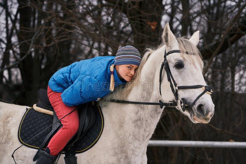 Cavaleiro da jovem mulher em um blazer azul e em ostentar um tampão para uma caminhada em um cavalo branco fotografia de stock royalty free