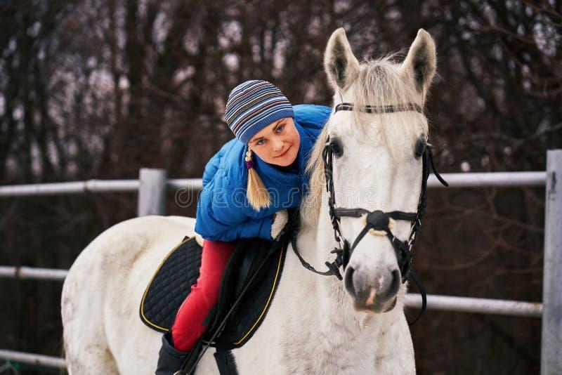 Cavaleiro da jovem mulher em um blazer azul e em ostentar um tampão para uma caminhada em um cavalo branco fotografia de stock