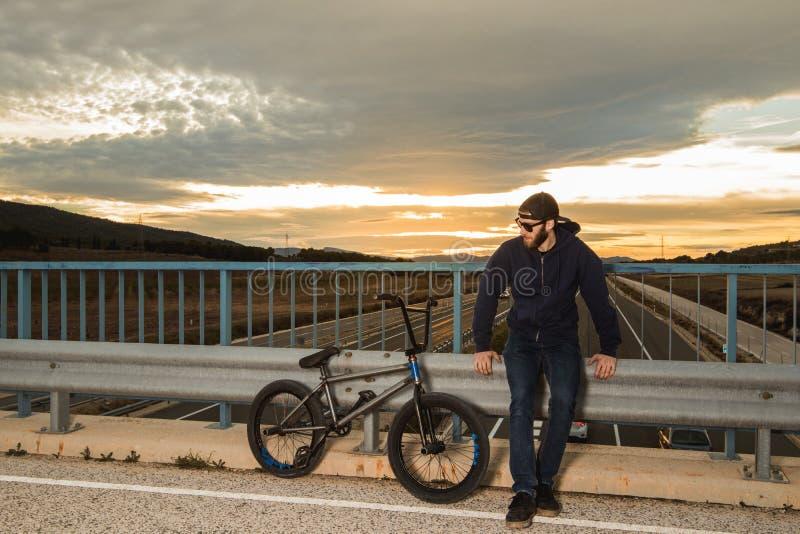 Cavaleiro de BMX com sua bicicleta do bmx na rua Equitação do indivíduo no bmx foto de stock royalty free