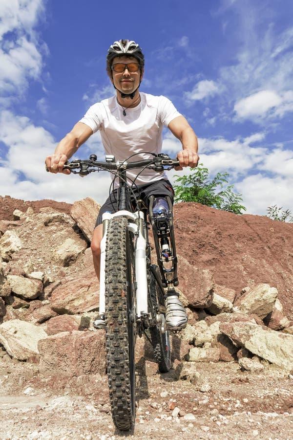 Cavaleiro deficiente do Mountain bike entre rochas imagens de stock