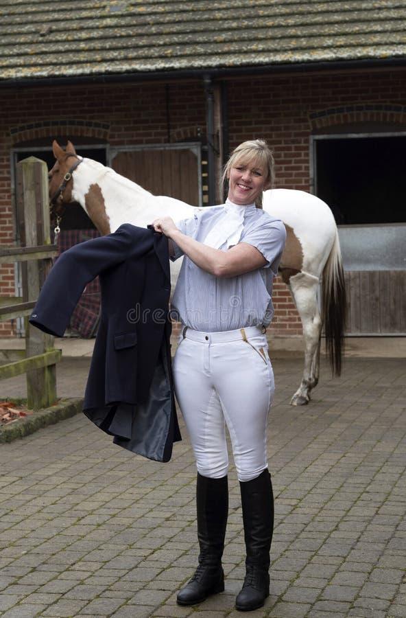 Cavaleiro do cavalo da mulher que obtém vestido fotos de stock