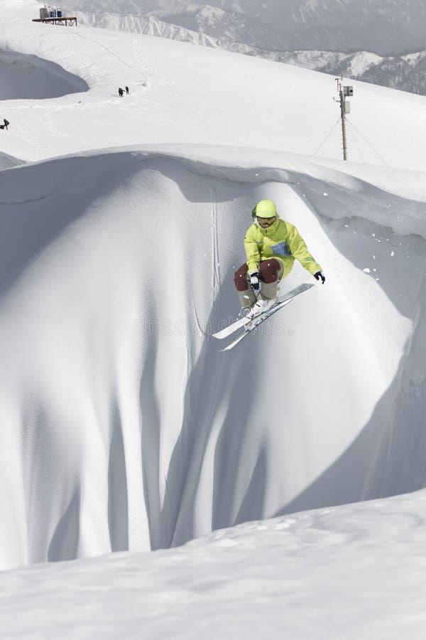 Cavaleiro do esqui que salta em montanhas Esporte extremo do freeride do esqui fotos de stock