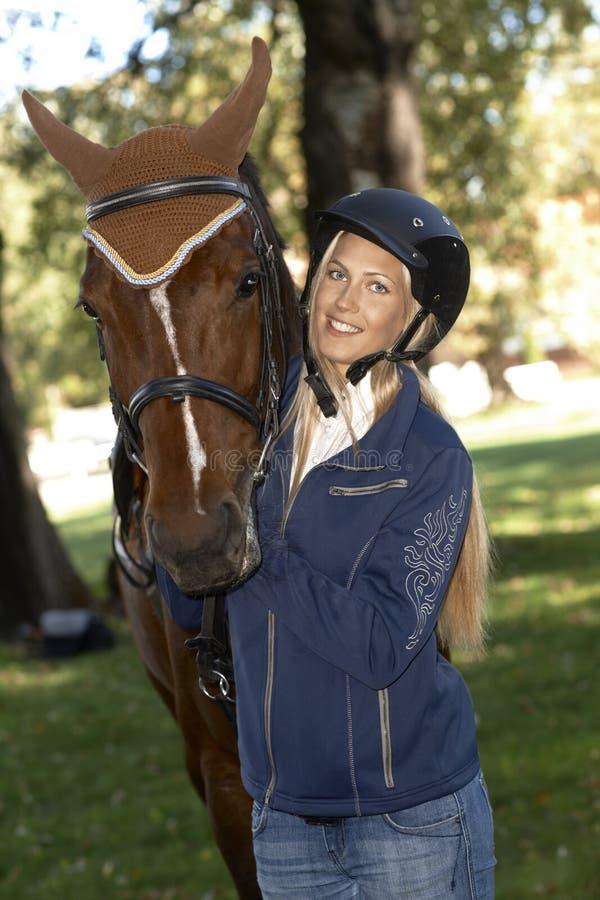Cavaleiro fêmea que abraça o sorriso do cavalo feliz foto de stock