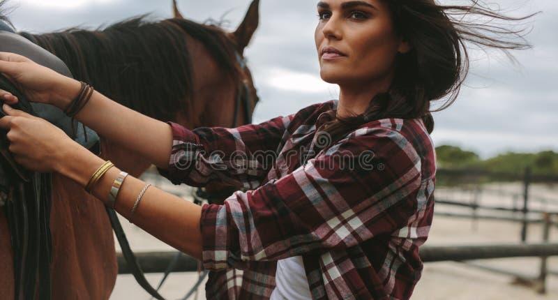 Cavaleiro fêmea que obtém o cavalo pronto para o passeio fotografia de stock royalty free