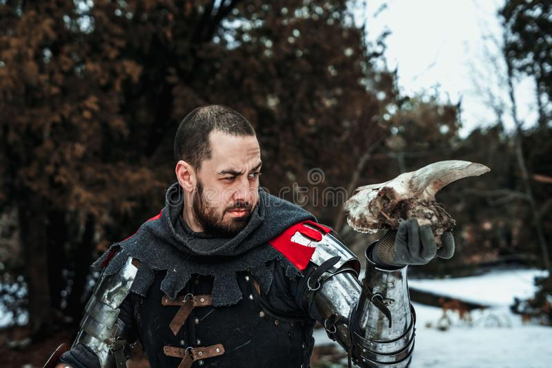 Cavaleiro masculino que guarda um crânio em sua mão imagem de stock royalty free