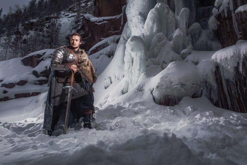 Cavaleiro medieval com a espada na armadura como o jogo do estilo do trono imagens de stock royalty free