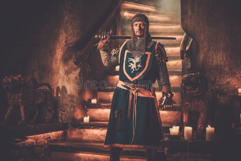 Cavaleiro medieval no protetor no interior antigo do castelo foto de stock royalty free
