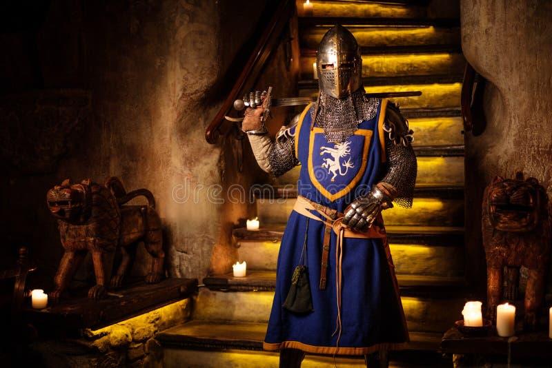 Cavaleiro medieval no protetor no interior antigo do castelo imagem de stock