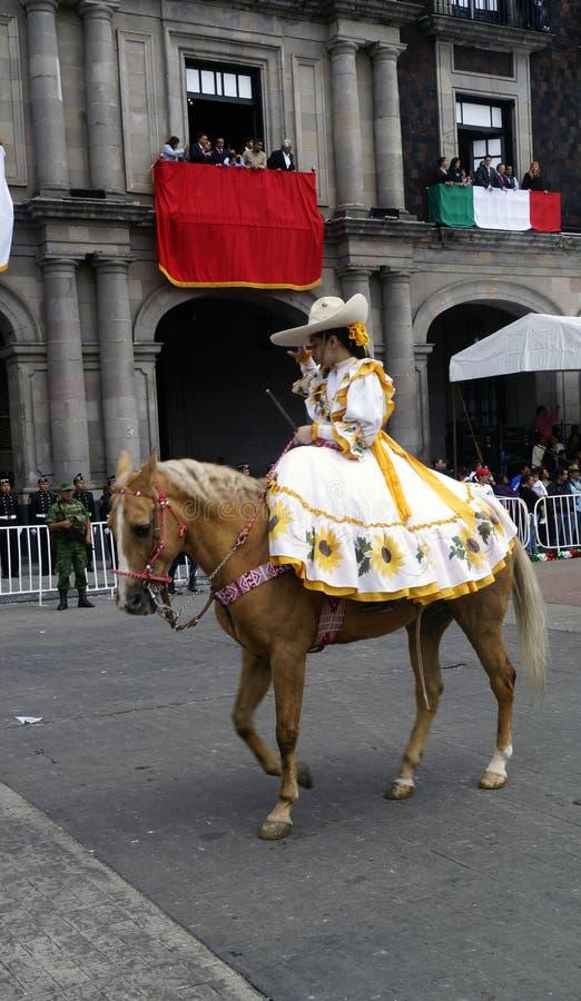 Cavaleiro mexicano da mulher na rua com vestido amarelo fotos de stock royalty free