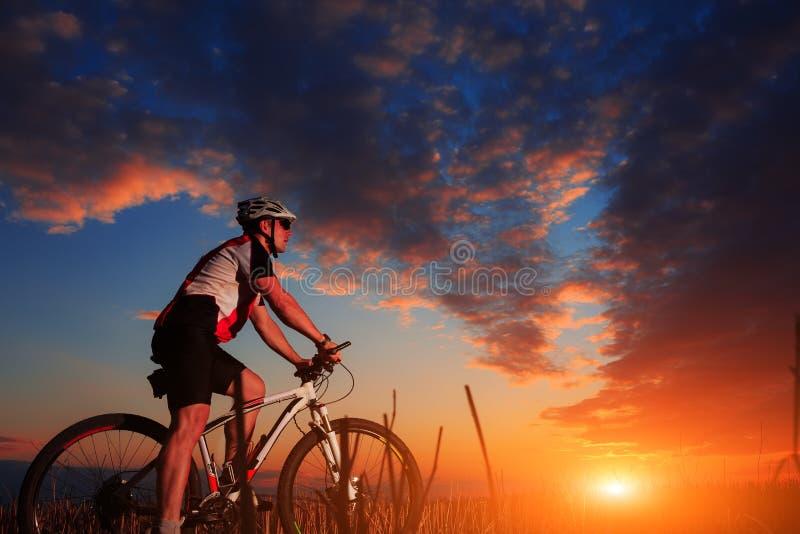 Cavaleiro na ação na sessão do Mountain bike do estilo livre imagem de stock