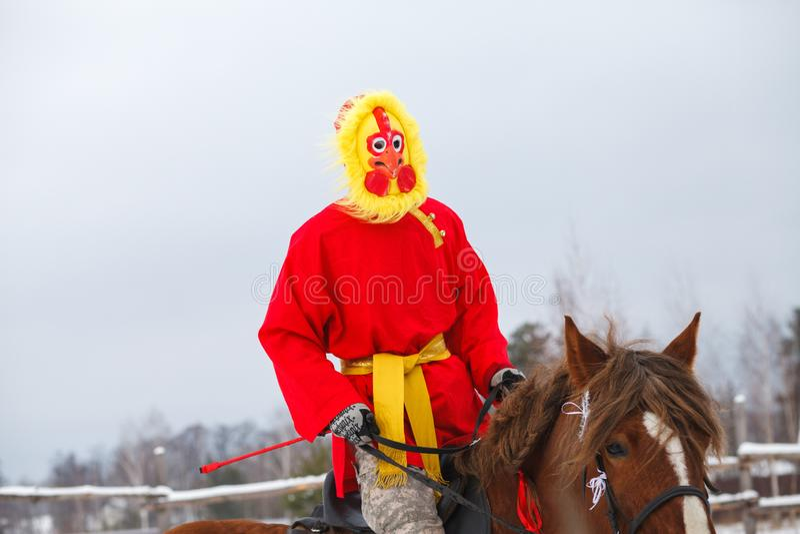 Cavaleiro vestido como um galo em um cavalo em um partido das crianças Shrovetide fotografia de stock