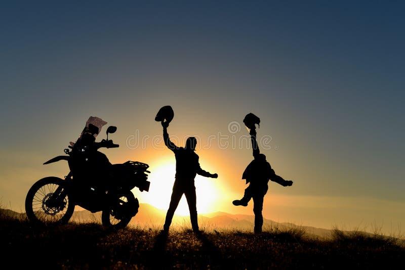 Cavaleiros da motocicleta no por do sol imagens de stock