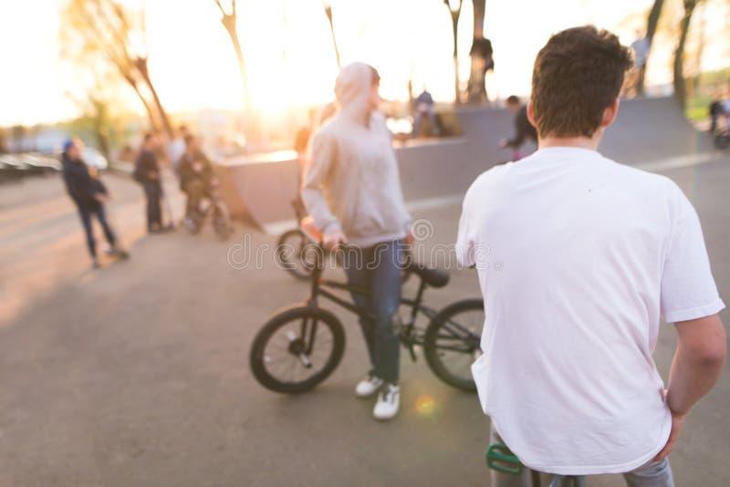 cavaleiros do bmx no parque do patim no fundo do por do sol Fundo com os ciclistas no bmx foto de stock