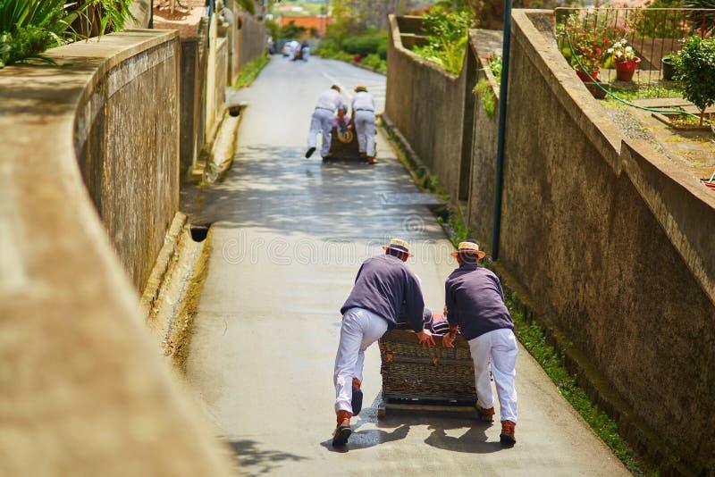 Cavaleiros do Toboggan que empurram o pequeno trenó de madeira para baixo em Funchal, ilha de Madeira, Portugal foto de stock royalty free