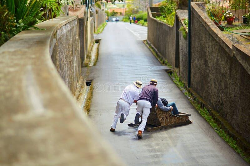 Cavaleiros do Toboggan que empurram o pequeno trenó de madeira para baixo em Funchal, ilha de Madeira, Portugal fotografia de stock royalty free