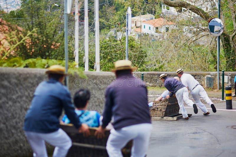 Cavaleiros do Toboggan que movem o pequeno trenó do bastão para baixo nas ruas de Funchal, ilha de Madeira imagens de stock royalty free