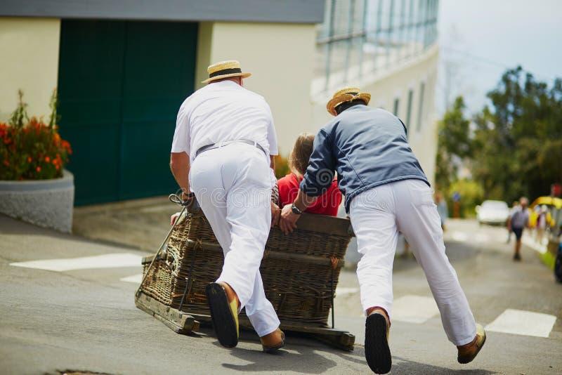 Cavaleiros do Toboggan que movem o pequeno trenó do bastão para baixo nas ruas de Funchal, ilha de Madeira fotos de stock royalty free