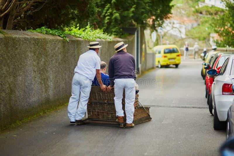 Cavaleiros do Toboggan que movem o pequeno trenó do bastão para baixo nas ruas de Funchal, ilha de Madeira foto de stock royalty free