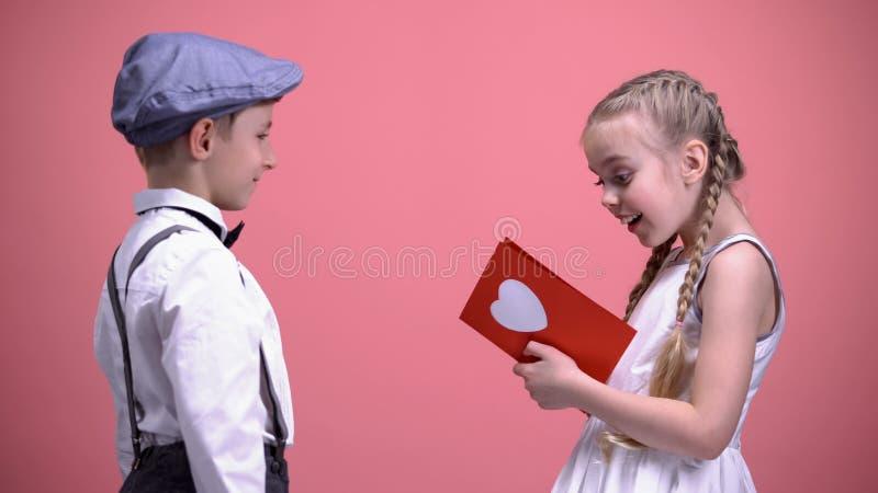 Cavalheiro bonito no desgaste do vintage que apresenta o vale-oferta do aniversário à menina surpreendida imagem de stock royalty free
