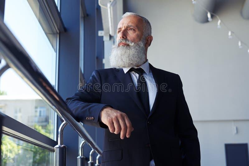 Cavalheiro concentrado com a barba cinzenta que olha para fora a janela imagem de stock