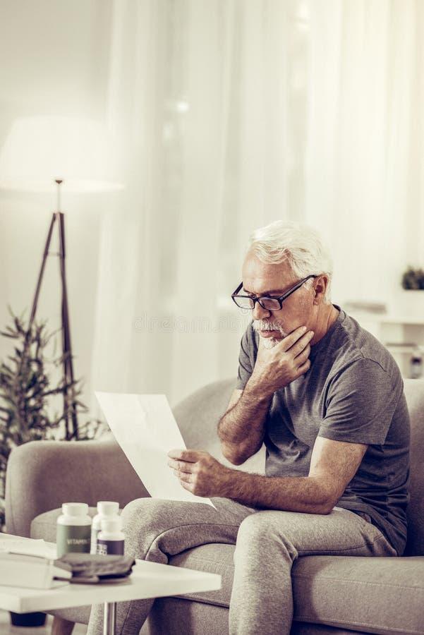 Cavalheiro considerável envelhecido que considera com cuidado documentos que realizando nas mãos imagem de stock