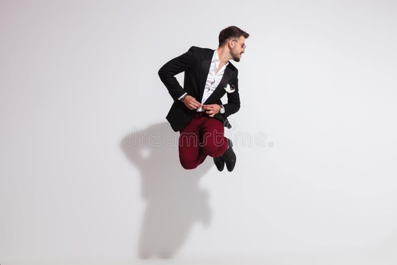 Cavalheiro engraçado que salta ao abotoar o terno e ao olhar ao lado foto de stock royalty free