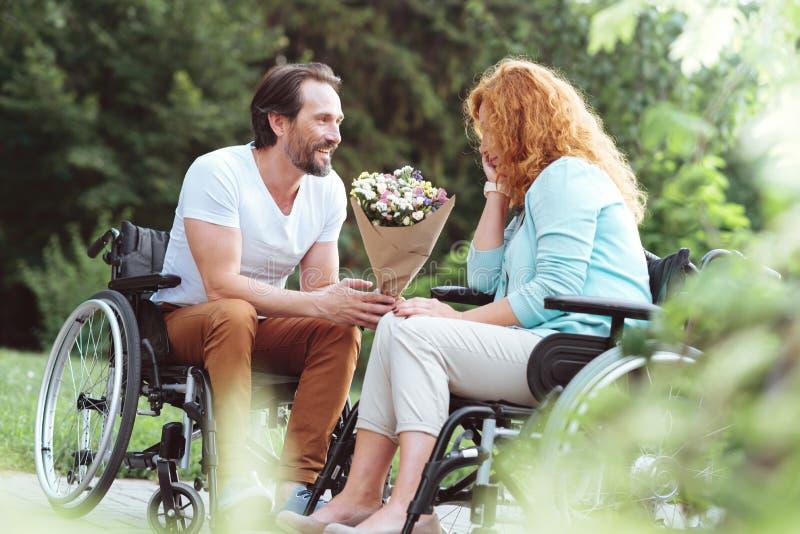 Cavalheiro loving que guarda flores e que fala a sua amiga imagem de stock