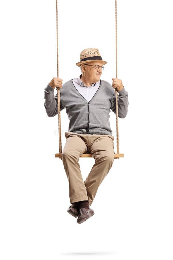 Cavalheiro maduro que senta-se em um balan?o e que olha ao lado fotografia de stock