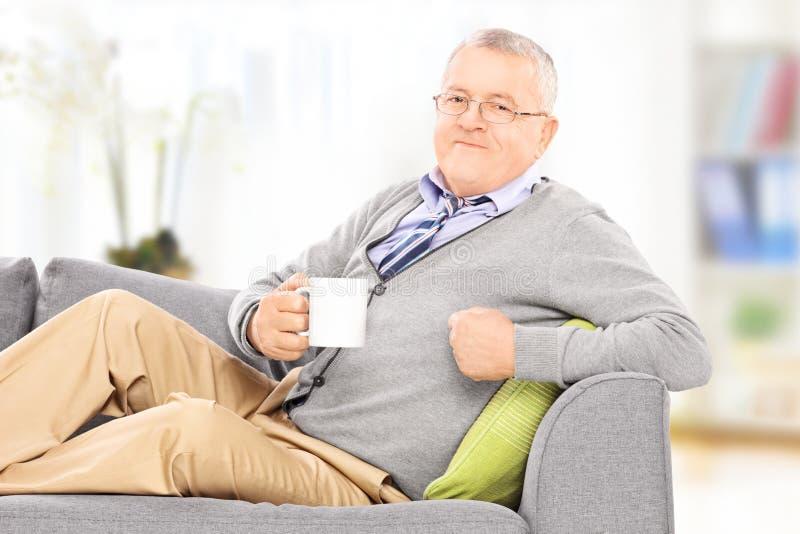 Cavalheiro relaxado que coloca no sofá e no café bebendo imagem de stock