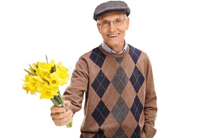 Cavalheiro superior de inquietação que guarda flores fotografia de stock