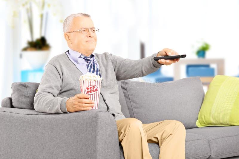 Cavalheiro superior em um sofá e em uma tevê de observação imagem de stock