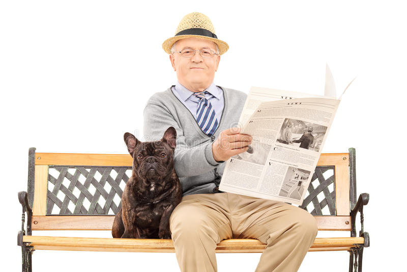 Cavalheiro superior que senta-se com seu cão e que lê o jornal foto de stock royalty free