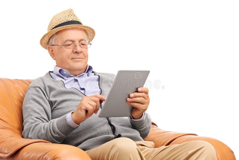 Cavalheiro superior que senta-se e que trabalha em uma tabuleta fotografia de stock