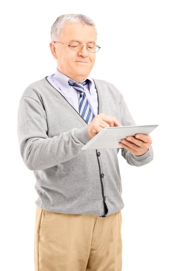 Cavalheiro superior que trabalha em uma tabuleta imagem de stock