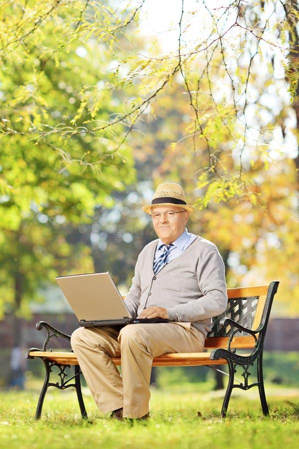 Cavalheiro superior que trabalha no portátil assentado no banco no parque imagem de stock royalty free