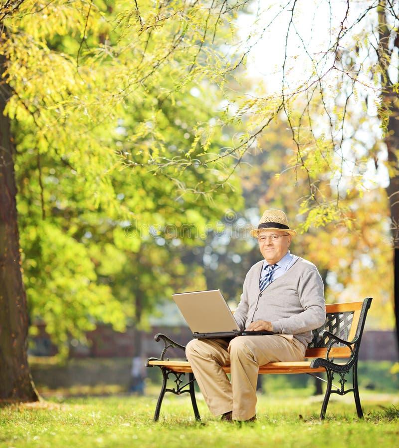 Cavalheiro superior que trabalha no portátil assentado no banco no parque fotos de stock royalty free