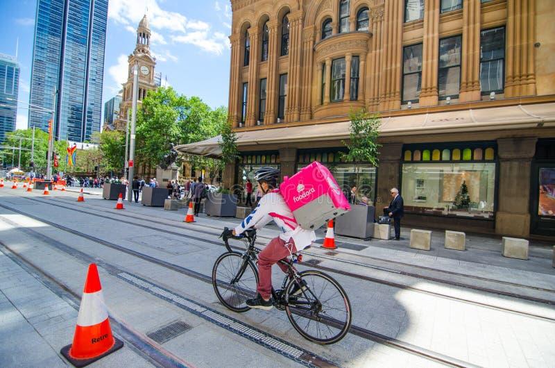 Cavalier de bicyclette de Foodora faisant le centre ville de la livraison de nourriture dedans de Sydney près du bâtiment de QVB photos stock