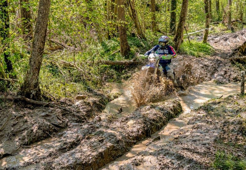 Cavalier de motocross éclaboussant la boue sur le terrain humide et boueux Concours généraux dans les motocross dans la province  image stock