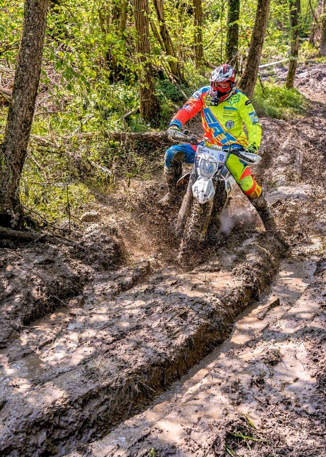 Cavalier de motocross éclaboussant la boue sur le terrain humide et boueux Concours généraux dans les motocross dans la province  image libre de droits