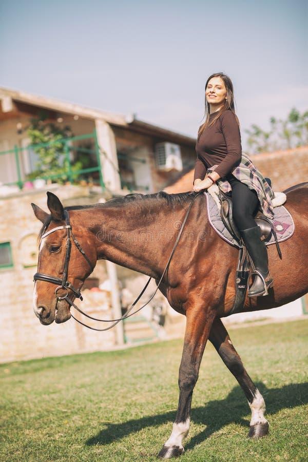 cavalier féminin attirant s'asseyant sur son cheval et sourire photos libres de droits