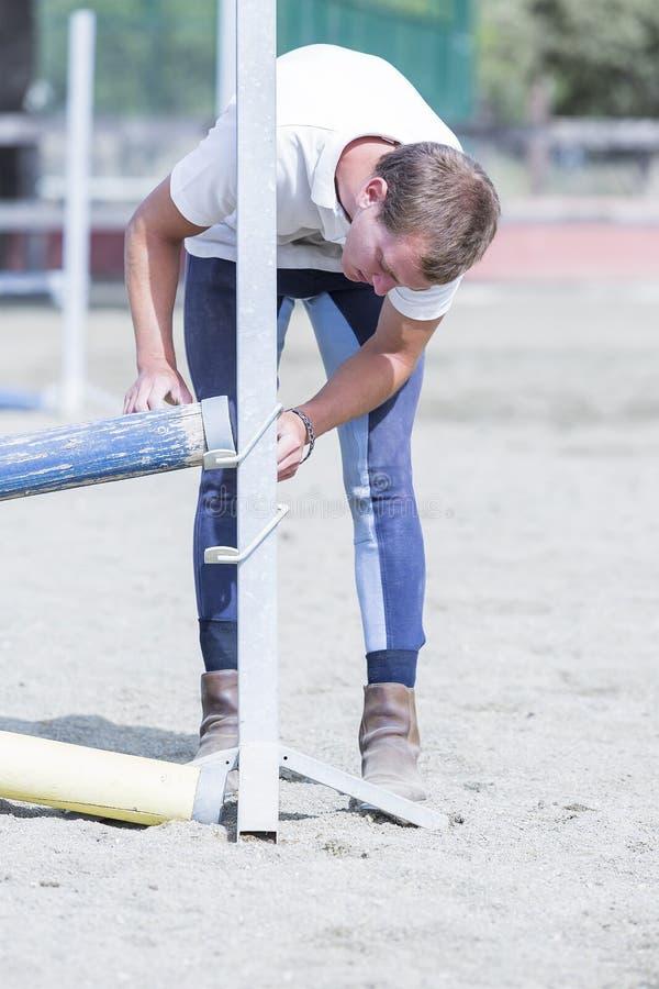 Cavaliere che dispone i pali di salto fotografie stock libere da diritti