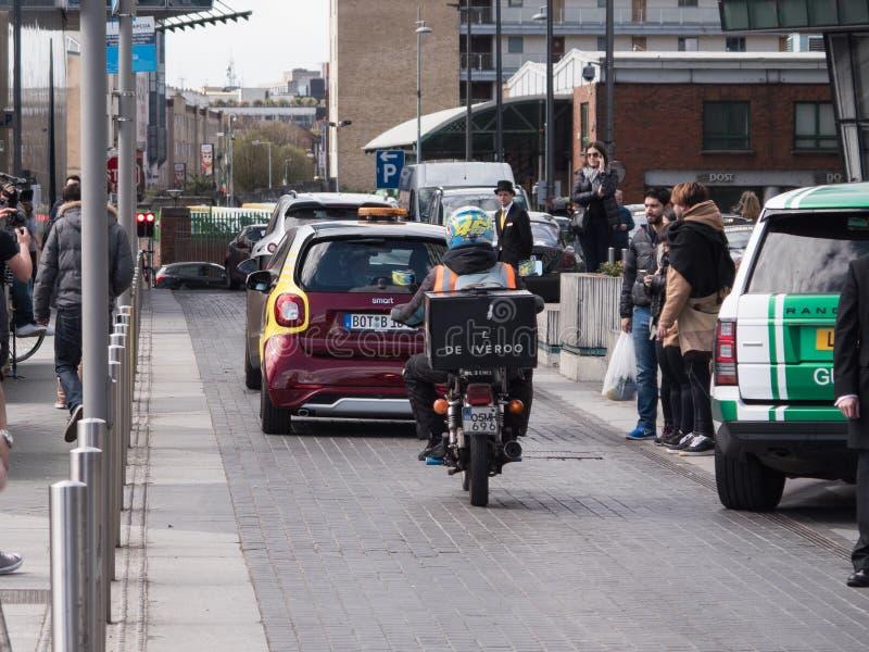 Cavaliere/corriere di consegna dell'alimento del motociclo nel traffico immagini stock