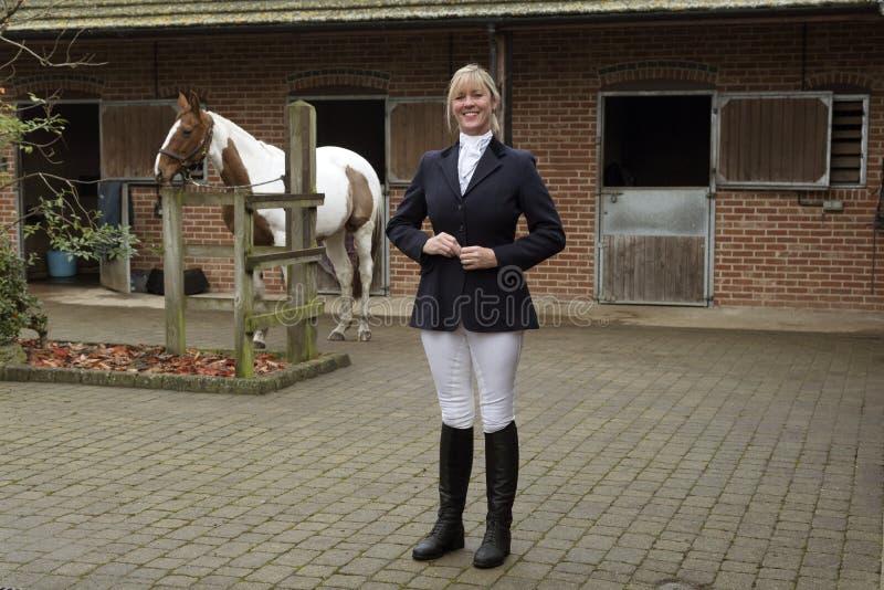 Cavaliere del cavallo della donna che sta in un'iarda stabile fotografia stock libera da diritti