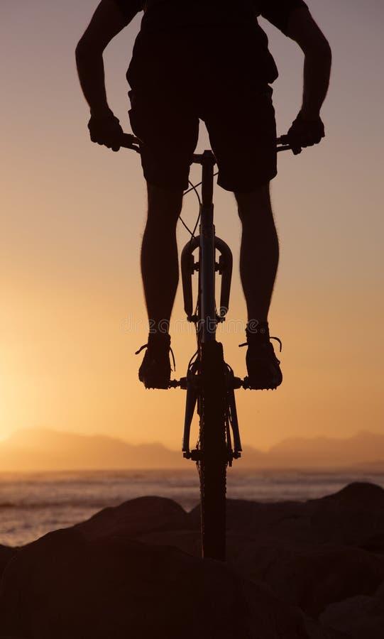 Cavaliere del mountain bike e tramonto Sudafrica fotografie stock libere da diritti