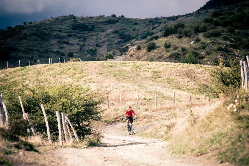 Cavaliere del mountain bike MTB sulla strada campestre, traccia della pista nel inspirat immagini stock libere da diritti