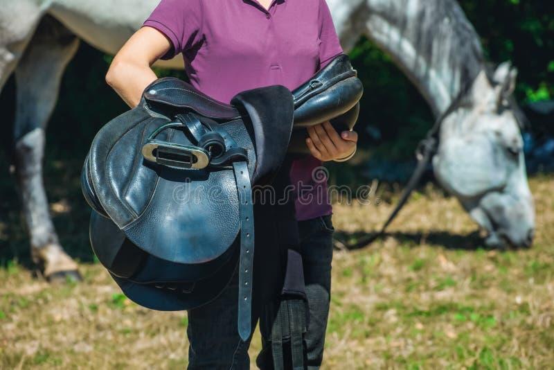 Cavaliere della ragazza che tiene un cavallo da sella nei precedenti che pasce animale fotografia stock
