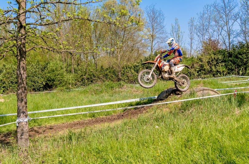Cavaliere di motocross nel salto dal trampolino sopra la strada Concorsi generali nei motocross in provincia di Varese fotografia stock libera da diritti