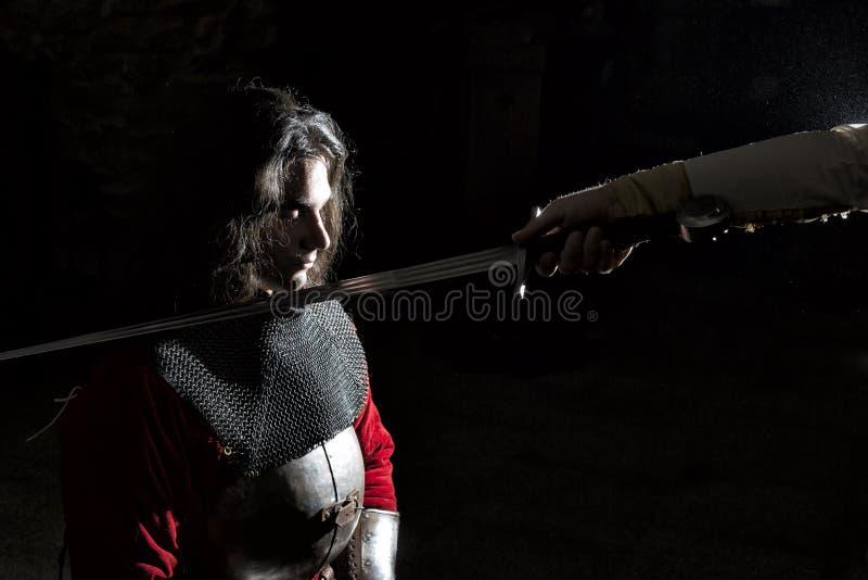 Cavaliere diventante Cerimonia-coraggioso Knighting del giovane, fondo nero fotografia stock
